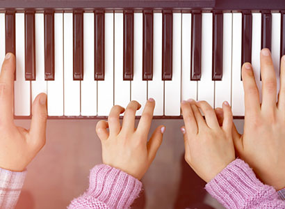 Kinderhände beim Klavierspielen
